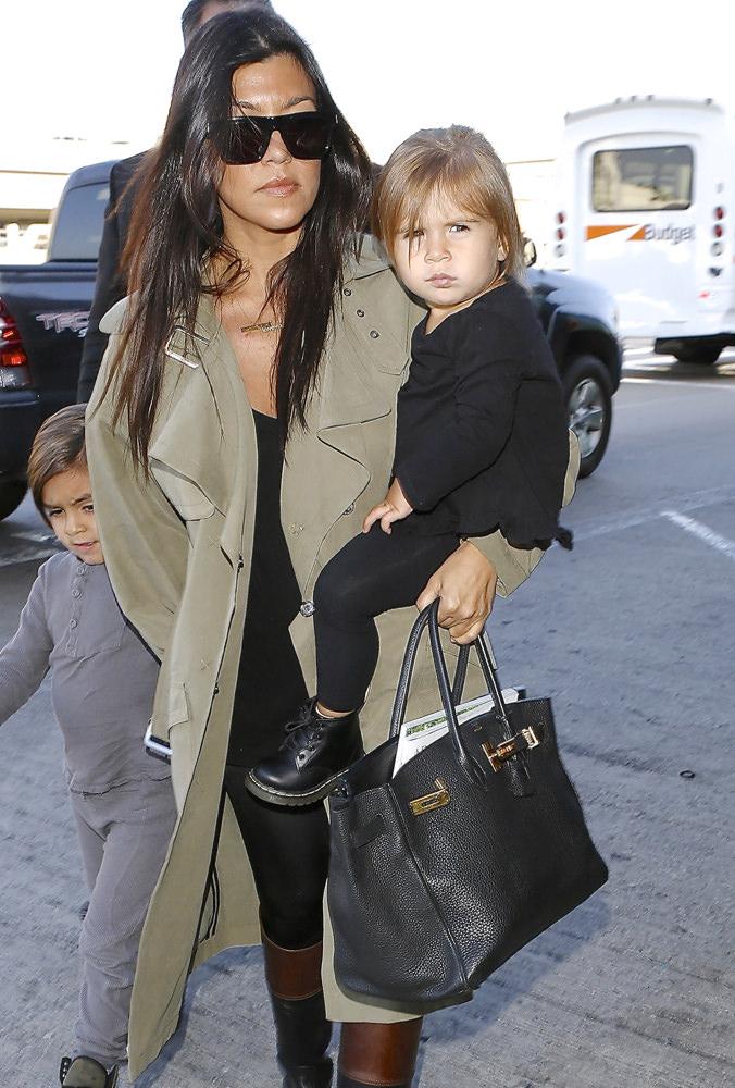 Reality star Kourtney Kardashian and kids were seen departing LAX for Kim's wedding